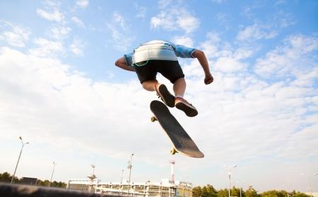 skate board: Skater jumps high in air on background blue sky