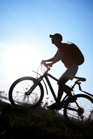 Silhouette of sports person cycling on the field on the beautiful sunset photo