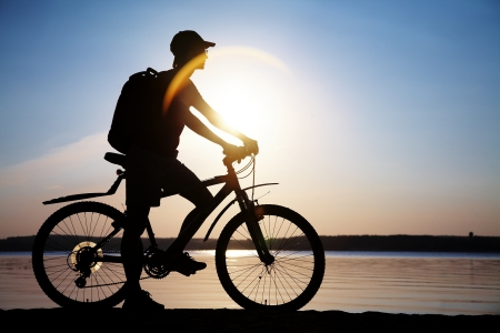 Silhouette of sports person cycling on the road on the beautiful sunset photo