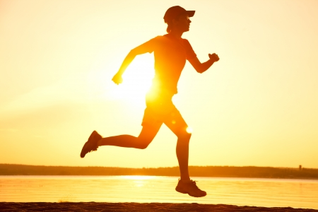 Young Female runner silhouette against the sunset Stock Photo - 14872823