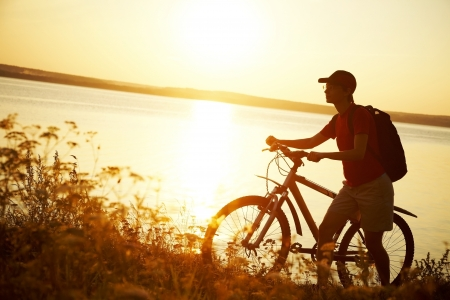 Silhouette of sports person cycling on the field on the beautiful sunset Stock Photo - 14872708