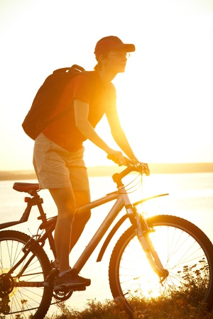 Silhouette of sports person cycling on the field on the beautiful sunset Stock Photo - 14872780