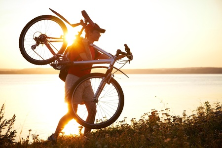 young cyclist is on the shoulder of his bike on the field at sunset photo