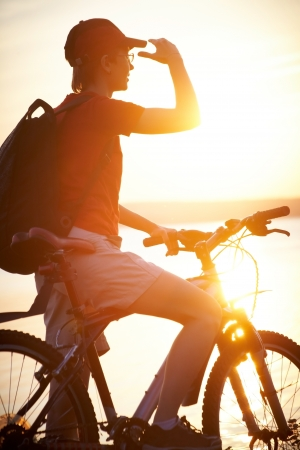 Silhouette of cyclist relaxing on the beautiful sunset photo