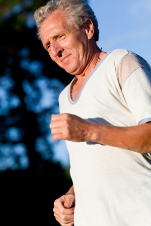 happy senior man running in the summer park photo