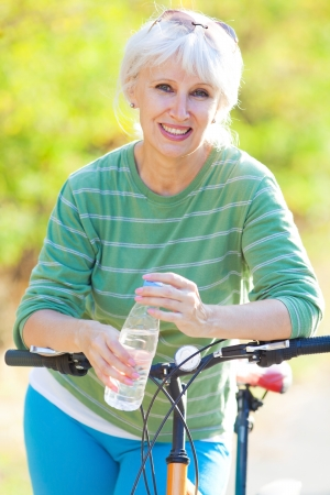happy senior woman cycling in the summer park photo