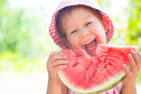 Watermelon: little girl eating a ripe juicy watermelon in summertime