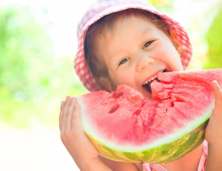 happyness: little girl eating a ripe juicy watermelon in summertime