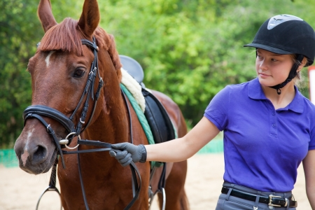 Portrait of young  horsewoman and brown horse photo