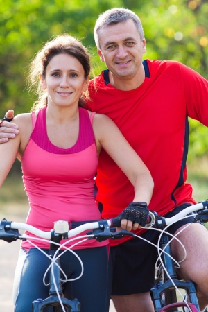 pareja madura feliz: feliz pareja madura montando una bicicleta en el parque verde Foto de archivo