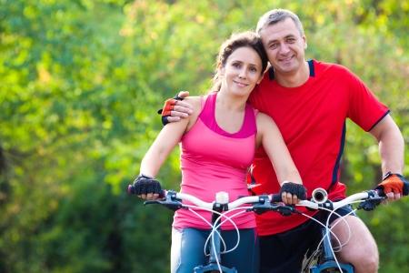 pareja saludable: feliz pareja madura montando una bicicleta en el parque verde Foto de archivo