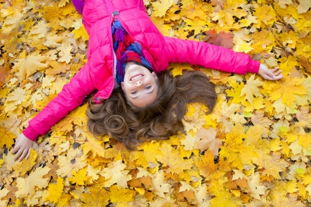 Horizontal image of a cheerful girl lying in autumn leaves Stock Photo