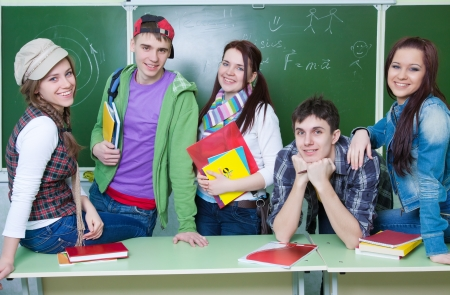 Portrait of six teens in classroom background green board photo