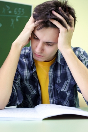 student put his hands over his head bent notebook on exam Stock Photo