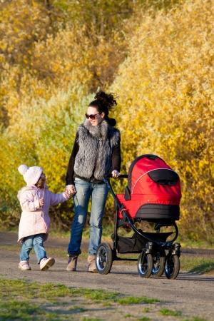 pram: Young mum walks with children in the autumn park