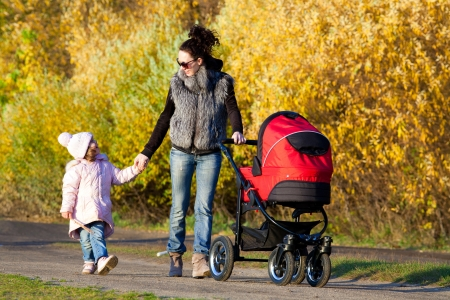 Young mum walks with children in the autumn park photo