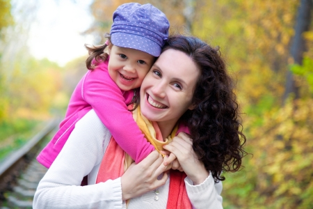 Portrait of smiling woman with cute little girl in autumn park photo