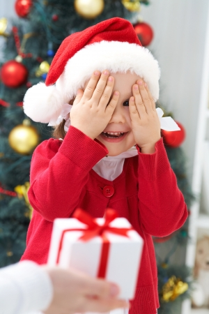 family celebration: Portrait of little cute girl with closed eyes waiting Christmas present