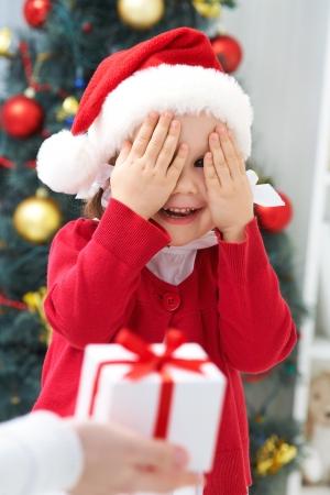 cajas navide�as: Retrato de ni�a linda con los ojos cerrados, esperando el regalo de Navidad Foto de archivo