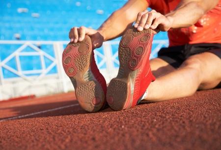 beine spreizen: junge Athlet sitzt auf dem Laufband Stadion gespreizten Beinen. Failure.
