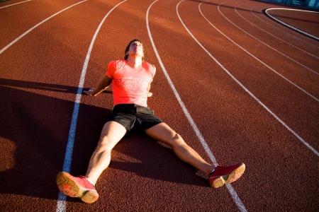 legs spread: atleta joven se sienta en las piernas del estadio rodante diseminado. Fracaso. Foto de archivo