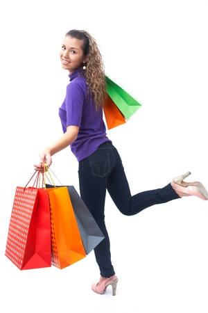cheerful young woman with shopping bags hurries to the shopping  photo