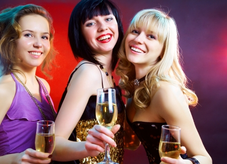 clandestine: Three young girls clink glasses of champagne at a party