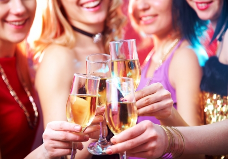 champagne glasses: Beautiful girls clink glasses of champagne at a party. unrecognizable people Stock Photo