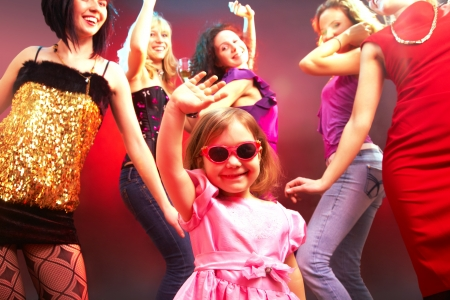The little girl's dancing in a disco surrounded by big girls photo