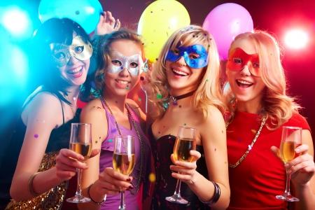 mascaras de carnaval: Danza chicas jóvenes felices bajo máscaras en el partido