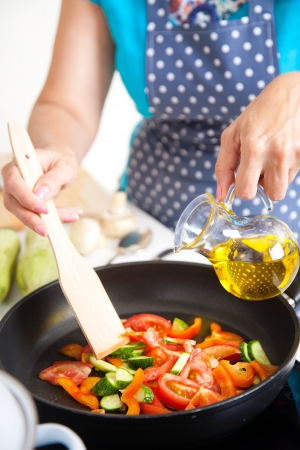 pans: Mature woman cooking dinner on the kitchen   Stock Photo