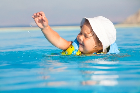 armbands: Funny little girl swims in a pool in yellow inflatable armbands