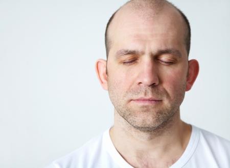 closed eyes: Portret van positieve kale lachende man op een witte achtergrond