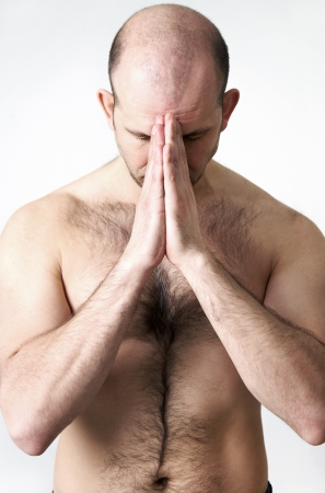 Portrait of man in studio with hands in prayer position photo