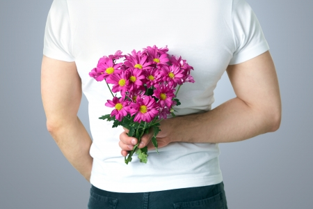 anniversary flowers: Man hiding a bouquet of flowers behind his back. unrecognizable Stock Photo