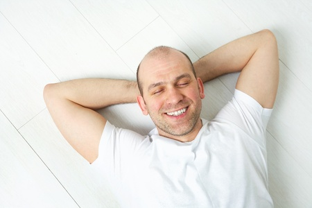 favourable: Portrait of happy bald-headed man on white floor Stock Photo