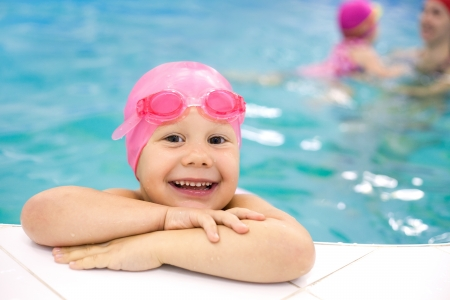 Portrait of little baby swimming  in swimming pool photo