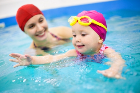 swimming to float: One year  baby girl at his first swimming lesson wiht mother