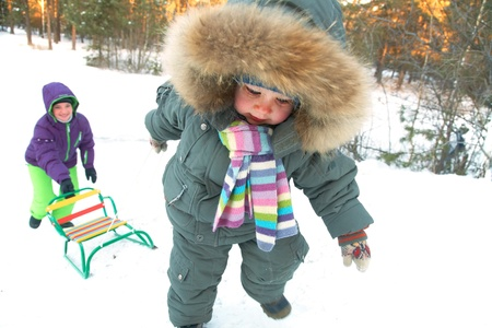 kids playing sports: little boy pulling sled in snowy hill with mom