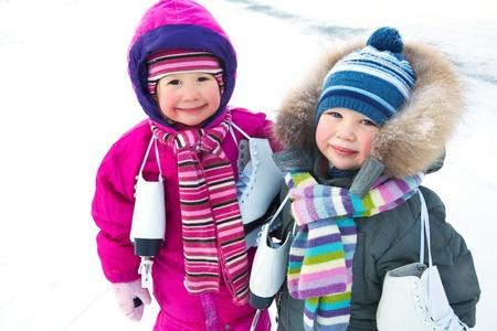 schaatsen: Kleine jongen en meisje met schaatsen in de winter backgruond sneeuw Stockfoto