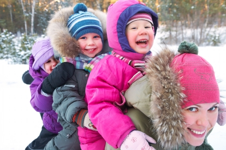 family and health: Young mother with  children playing on snow in winter time