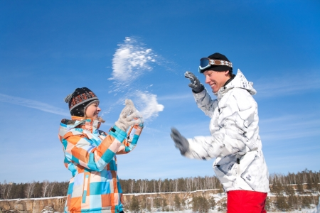 Young playful couple having fun in the snow photo