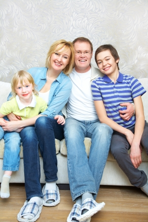 Portrait of family sitting in living room smiling to camera photo