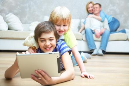 net surfing: Due bambini che giocano con il computer portatile sul pavimento. I genitori seduti sul divano. Messa a fuoco selettiva ai bambini.