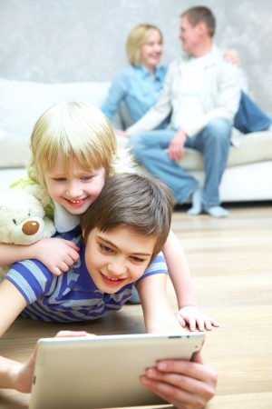 enjoyment: Two children playing with laptop on floor.  Parents sitting on sofa. Selective focus to children.