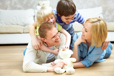 lying on the floor: Portrait of family lying on floor living room and smiling to camera Stock Photo