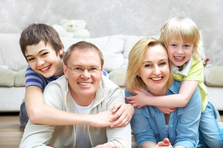 family living: Portrait of family lying on floor living room and smiling to camera Stock Photo