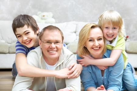 familia abrazo: Retrato de familia tumbado en piso sala de estar y sonriendo a la c�mara