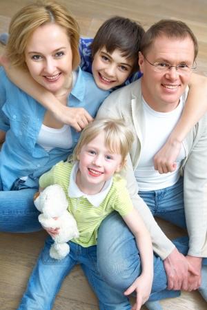 mujer hijos: Retrato de familia tumbado en el suelo en casa Foto de archivo
