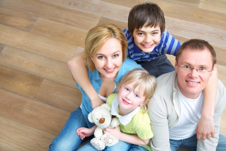 Portrait of family lying on floor in home photo